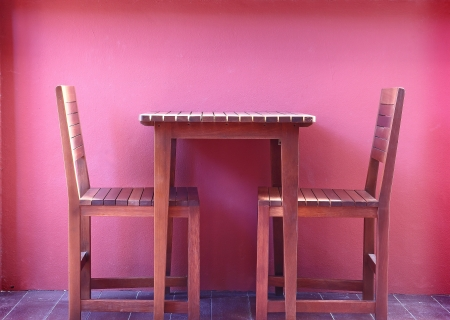 Wooden chairs with red wall Stock Photo