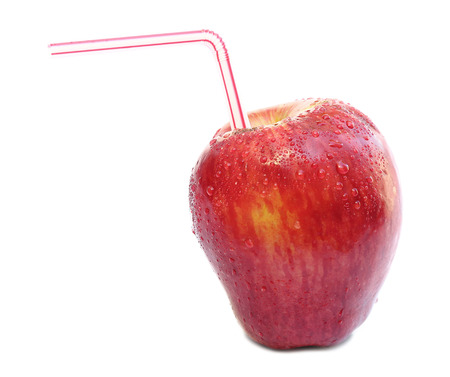 Red apple with water drops and a straw isolated on white