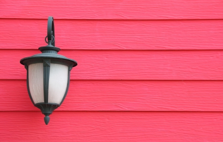 Lamp hanging on red wooden wall background Stock Photo
