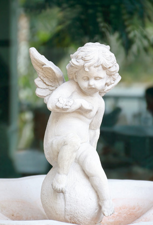 Cupid statue sitting  Stock Photo