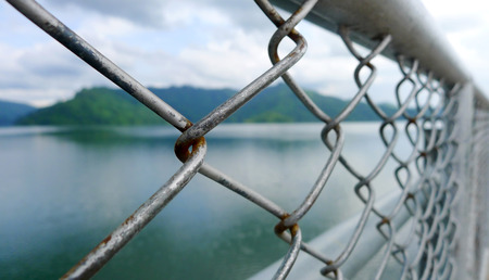 Old metal fence with mountain and lake backdrop