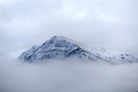 steep: Mountain peak breaking through the solid cloud bank