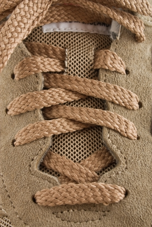 knotted shoelaces on suede running shoes closeup photo