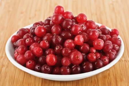 fresh cranberries on a plate, against a wooden board Stock Photo - 16320408