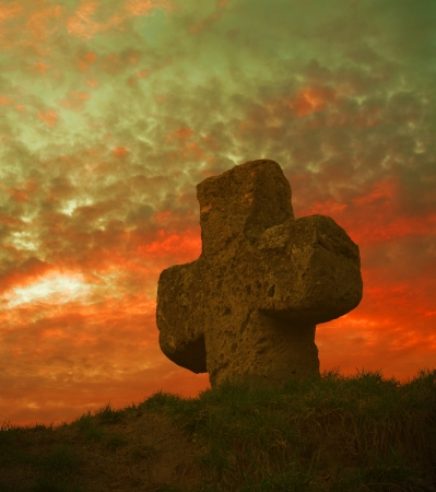 old stone cross on the background of a beautiful sunset Stock Photo - 16320222