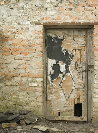 damaged houses: old door on a brick wall background