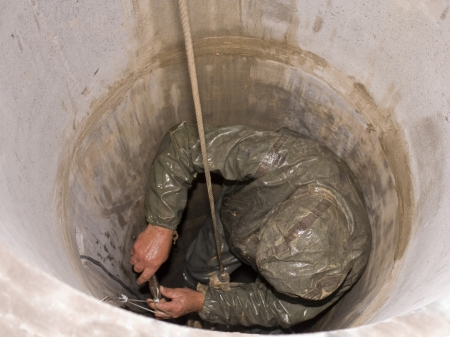 person performs work in the sewers photo