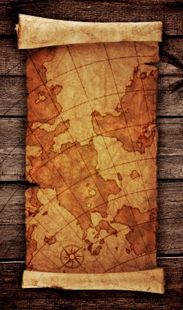 ancient scroll map, on the old wooden background  photo
