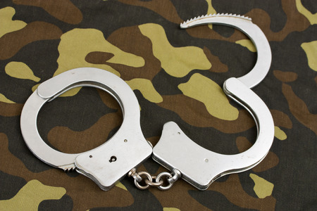 restraints: handcuffs on camouflage fabric background