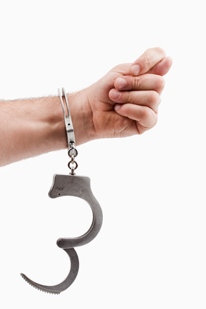 One hand in handcuffs, with one cuff unlocked isolated over white photo
