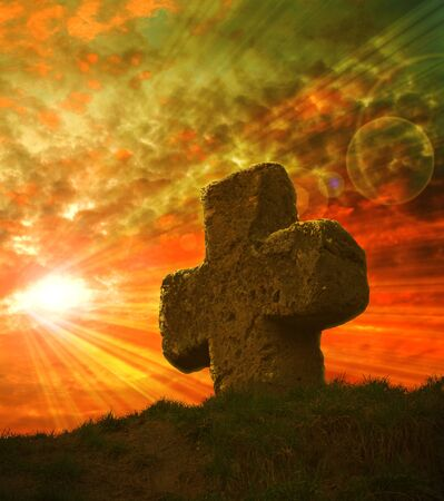 old stone cross on the background of a beautiful sunset Stock Photo