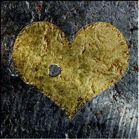 gold metallic grunge pierced heart on a dark metallic background Banco de Imagens