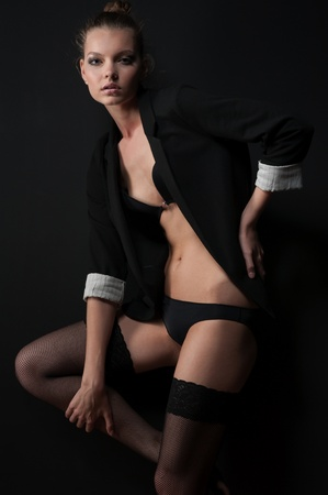 Slim girl in the background of a black wall in stockings and underwear Stock Photo - 8673887
