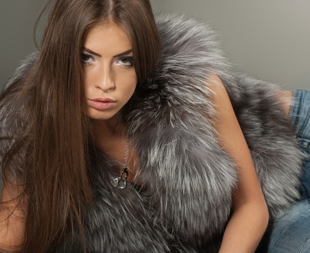 Graceful brunette posing in jeans and fur photo