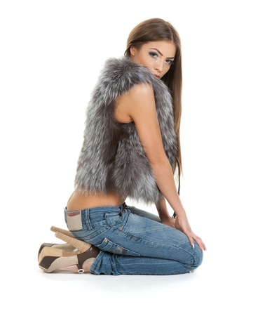 Brunette in fur sitting on white background photo