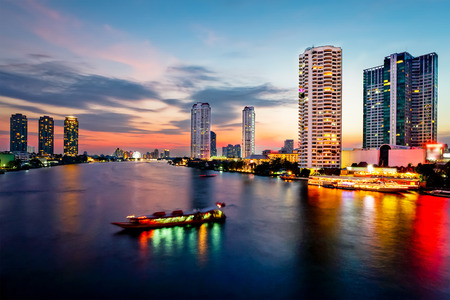 Bangkok Transportation at Dusk with Building along the river (Thailand) photo