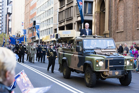 armed services: The RSL president smiles at the crowd while standing in the back of an army jeep as they drive down along Elizabeth