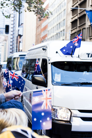 armed services: White taxi bus carrying veterans drives past the flag waving crowd