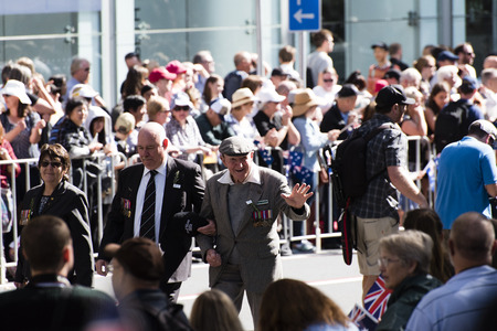 armed services: Smiling veteran being assisted by a younger man waves at the crowd as they walk down Elizabeth St