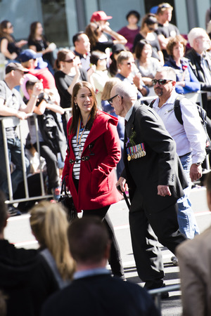 armed services: Veteran with a walking stick talks to a young woman in a red coat as they march past the crowd down Elizabeth St Editorial