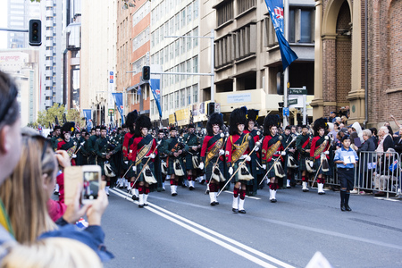 bagpipes: The first drum and pipe marching band passes by the crowd along Elizabeth St Editorial