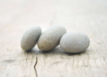 three round and soft stones on a old piece of wood Standard-Bild