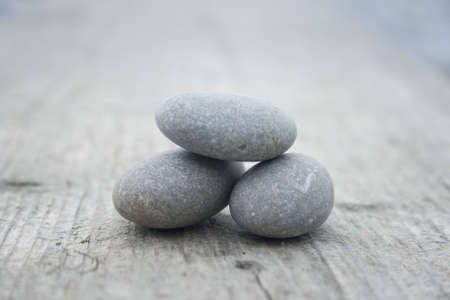 three round and soft stones on a old piece of wood photo