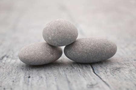 piedras zen: tres piedras redondas y suaves sobre una antigua pieza de madera