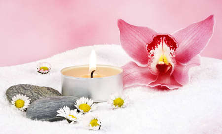 two towels with a pink orchid and two candels