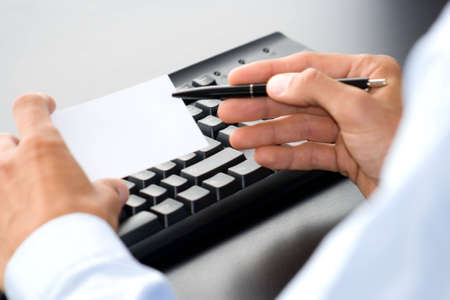 hand with white card in front of a computer keyboard Stock Photo