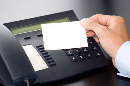 hand with white card and a telephone Stock Photo
