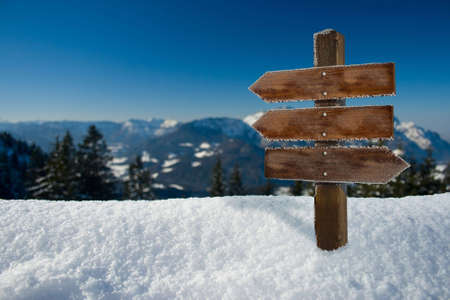 panorama of the alps with a wooden sign Standard-Bild