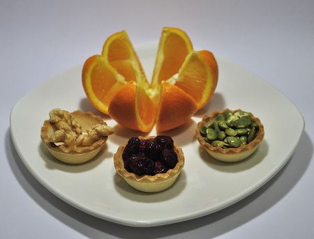 Open orange and tartlets of blueberries, pips and nuts Stock Photo