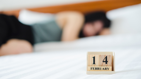 Alone woman sleeping on white bed with 14 February wooden calendar in Valentine day. Broken heart and sad concept. Stock Photo