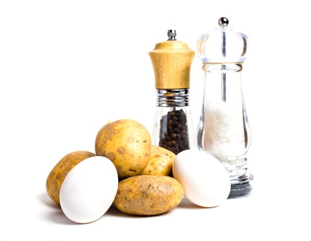 New potatoes, eggs and salt and pepper shakers isolated on white background photo