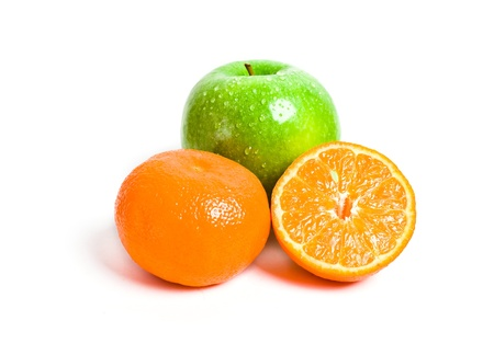 Juicy cut orange and green apple isolated on white background