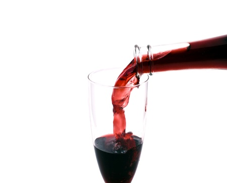 red wine pouring in the glass from the bottle on white background