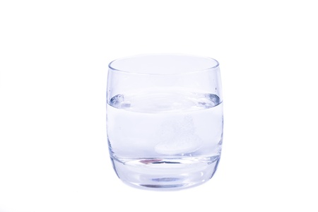 aspirin dissolving in the glass of water isolated over white background