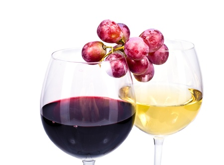 pair of wine glasses with red and white wine and grapes isolated over white background