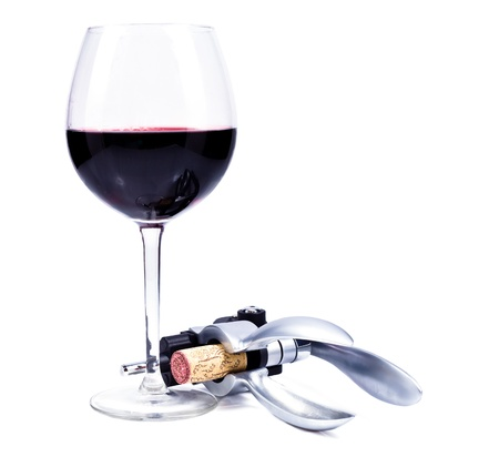 wine glass with red wine and bottlescrew isolated over white background