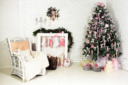 Nice Christmas interior with a fir tree, armchair and gifts Stock Photo