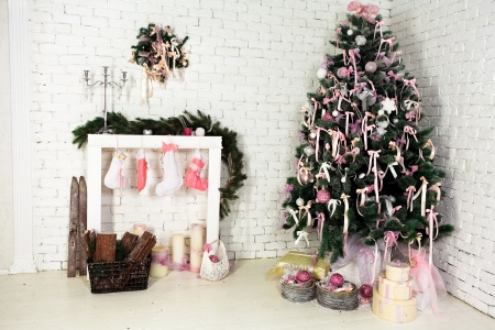 Nice Christmas interior with a fir tree, fireplace and gifts photo