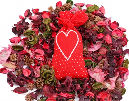red sachet with a heart in the background of petals over white Stock Photo - 17596522
