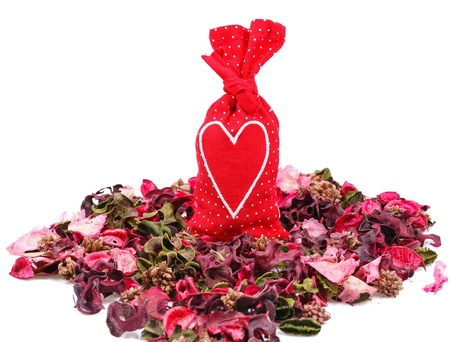 red sachet with a heart in the background of petals over white Stock Photo - 17596555