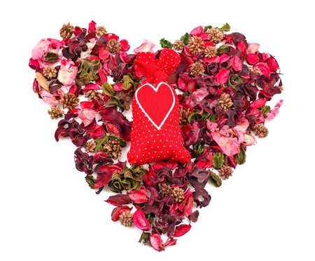 heart shaped stuff: red sachet with a heart in the background of petals in the form of a heart over white Stock Photo