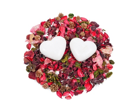 two gingerbread hearts in the background of sachet petals over white Stock Photo - 17596559