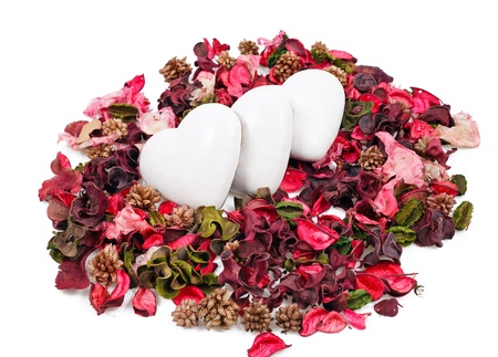 three gingerbread hearts in the background of sachet petals over white