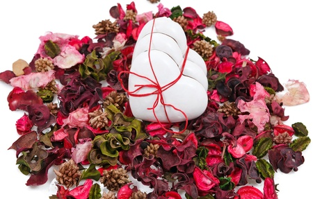 three gingerbread hearts in the background of sachet petals over white photo