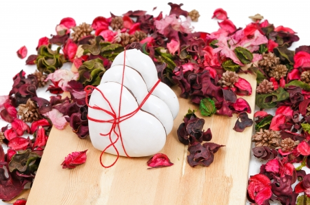 three gingerbread hearts in the background of sachet petals on wooden background