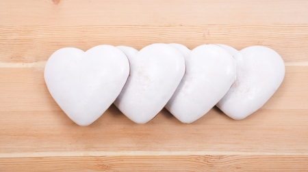 four white gingerbread hearts on wooden background